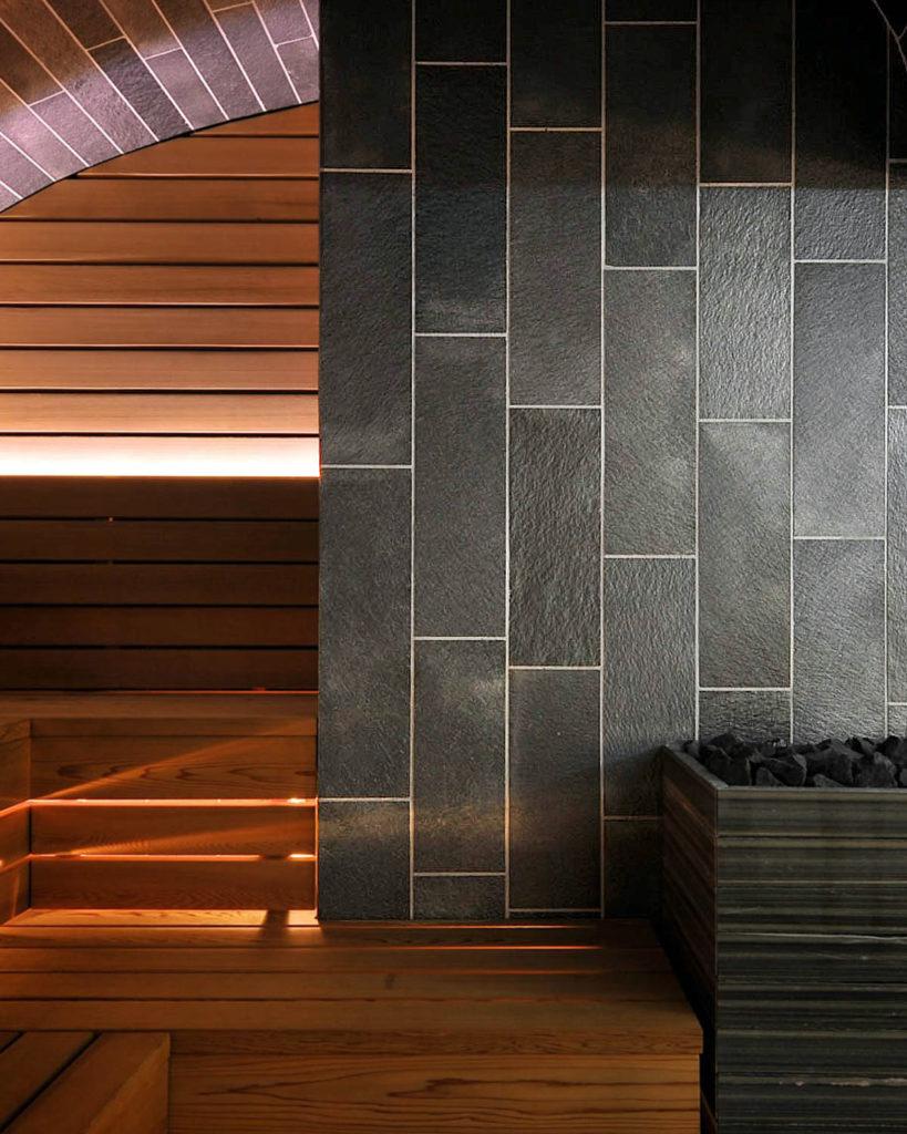 En badstu / sauna med vegger og tak av skifer fliser av Offerdalskifer. Badstuovnen er bekledt med et stykke fra en massiv skiferplate fra Offerdal
