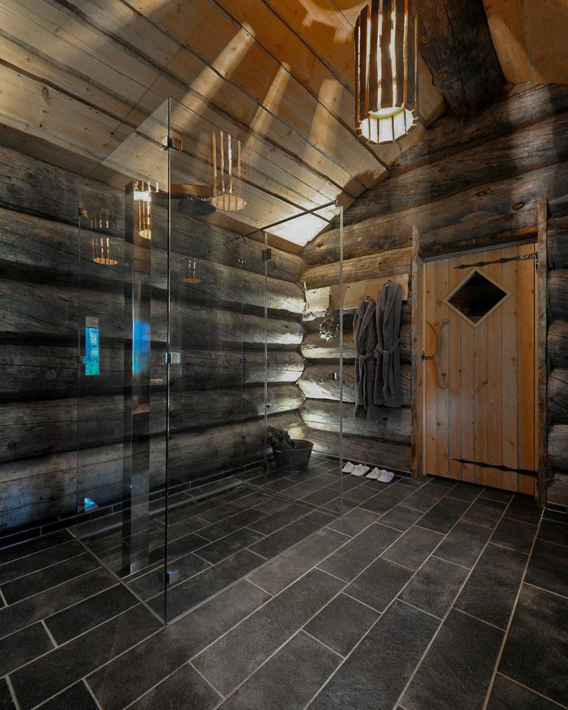 Et rustikt bas med gråe rundtømmervegger og fliser på gulvet av Offerdalskifer. Det er en inngang til en sauna / badstu innerst