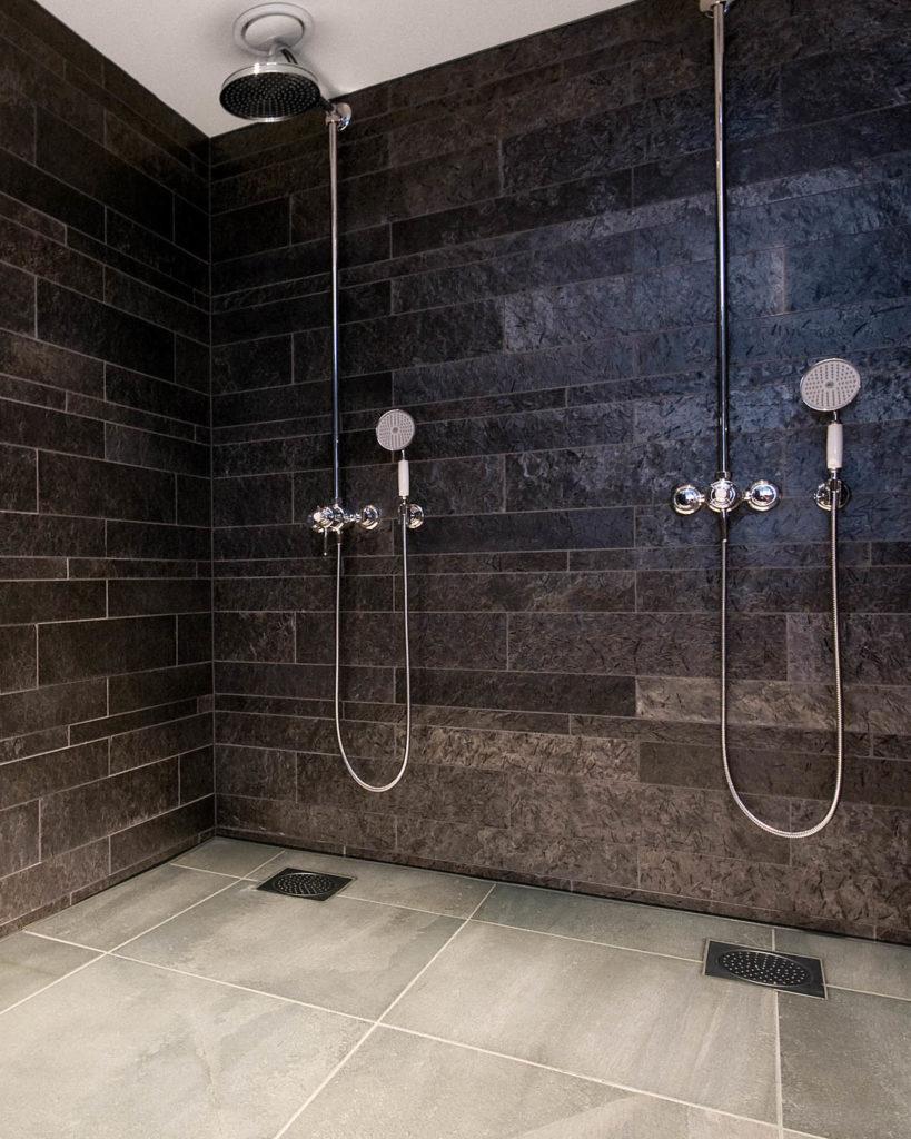 En dusj med to dusjhoder. På veggen er det smale fliser i ulike høyder av Ottaskifer og på gulvet fliser i storformat av lys Oppdal silkebørstet skifer