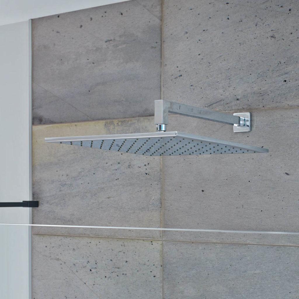 Et detaljbilde av en regndusj med fliser av silkebørstet fliser av skifer på gulv og på dusjvegg.