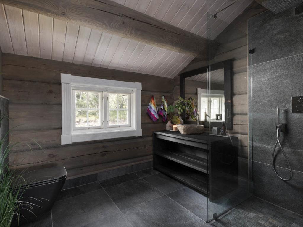 Et bad på en hytte med mørke fliser og grønn beplantnng