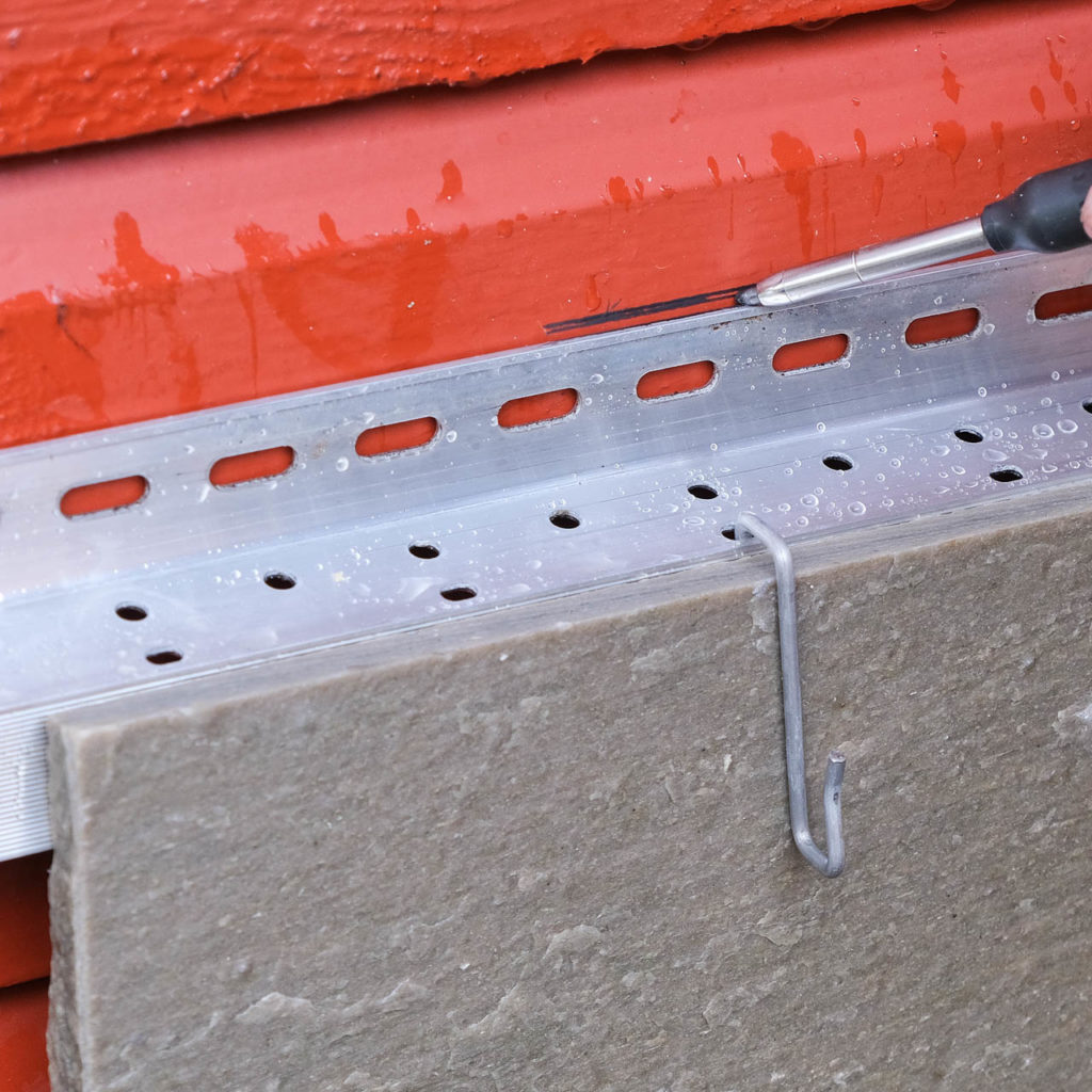 Oppheng av fasadeskifer med aluminiumskinner og kroker på hytteveggen.