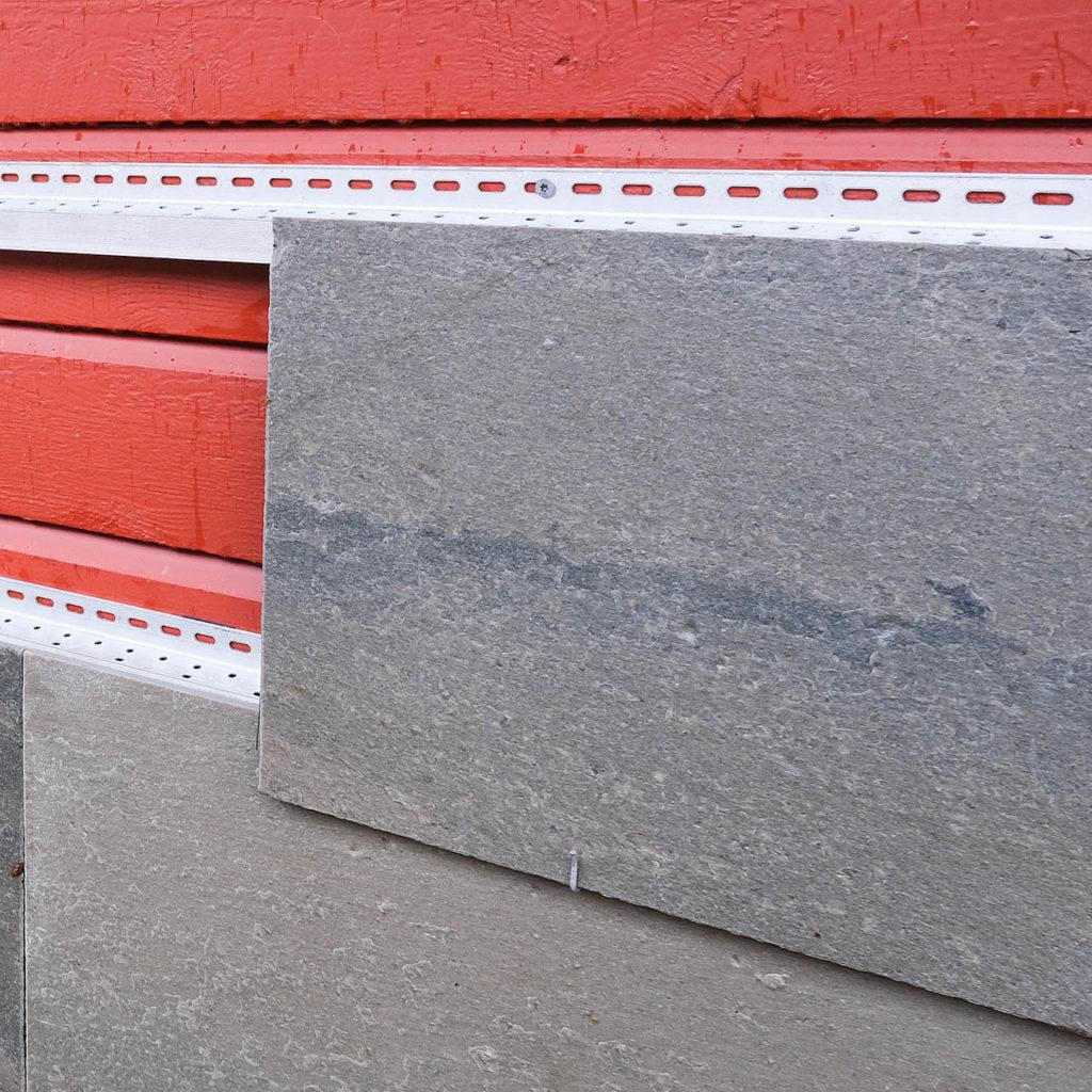 Oppheng av tynne skiferplater på fasaden med aluminiumsskinner og kroker.
