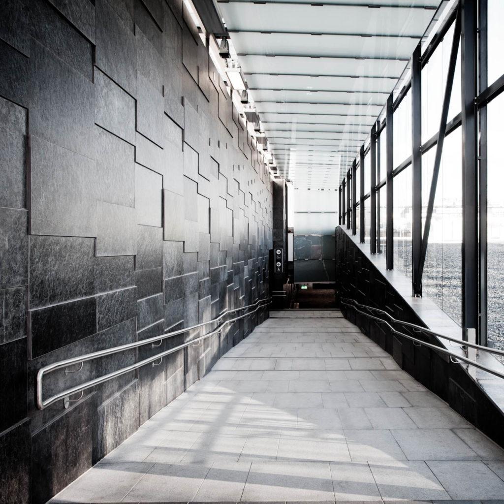 Nedgang til T-bane med Otta fasadeskifer og glass. De sorte skiferplatene i ulike format gir et mønster på veggen.