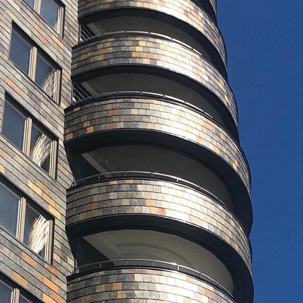 Et høyt leilighetsbygg med runde balkonger kledt med fasadeskifer fra Otta Pillarguri i gylne farger av rust og sort.
