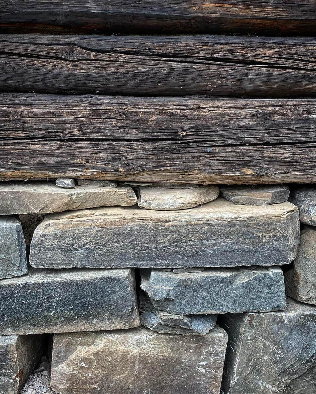 En grunnmur i skifer fra Offerdal med en bygningskropp av gammelt tømmer