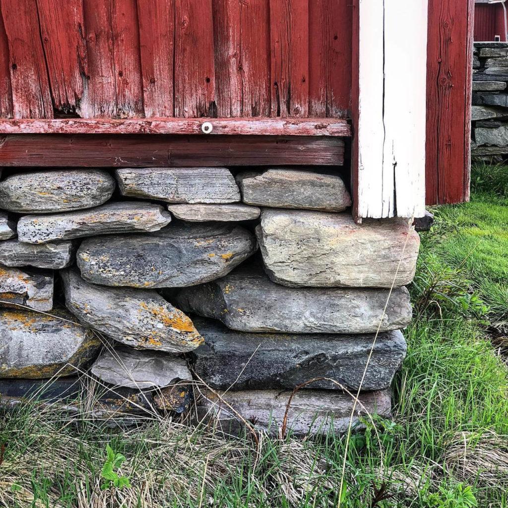En grunnmur i naturstein med en bygningskropp av gammelt tømmer