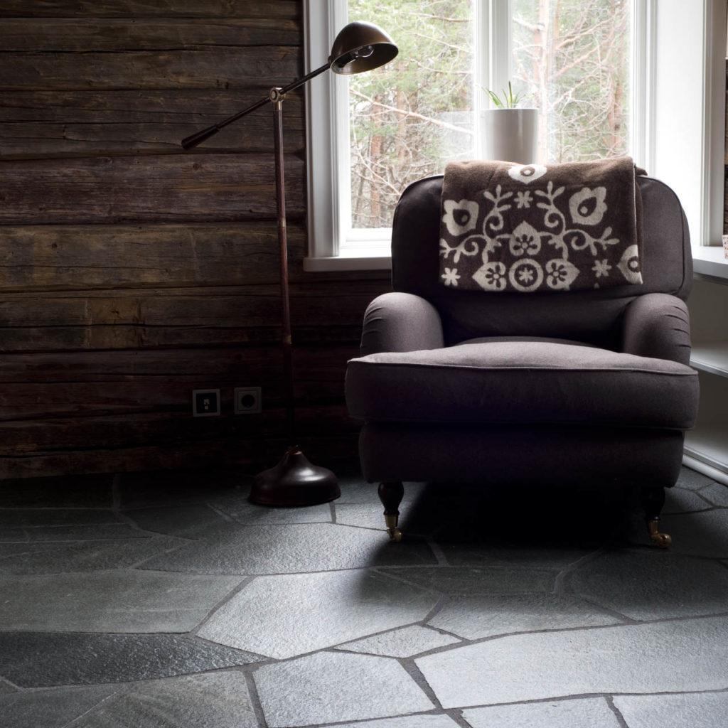 Et rom med rustikke mørke tømmervegger og en mørk stor lenestol. På gulvet er det grå bruddskifer fra  Offerdalskifer.