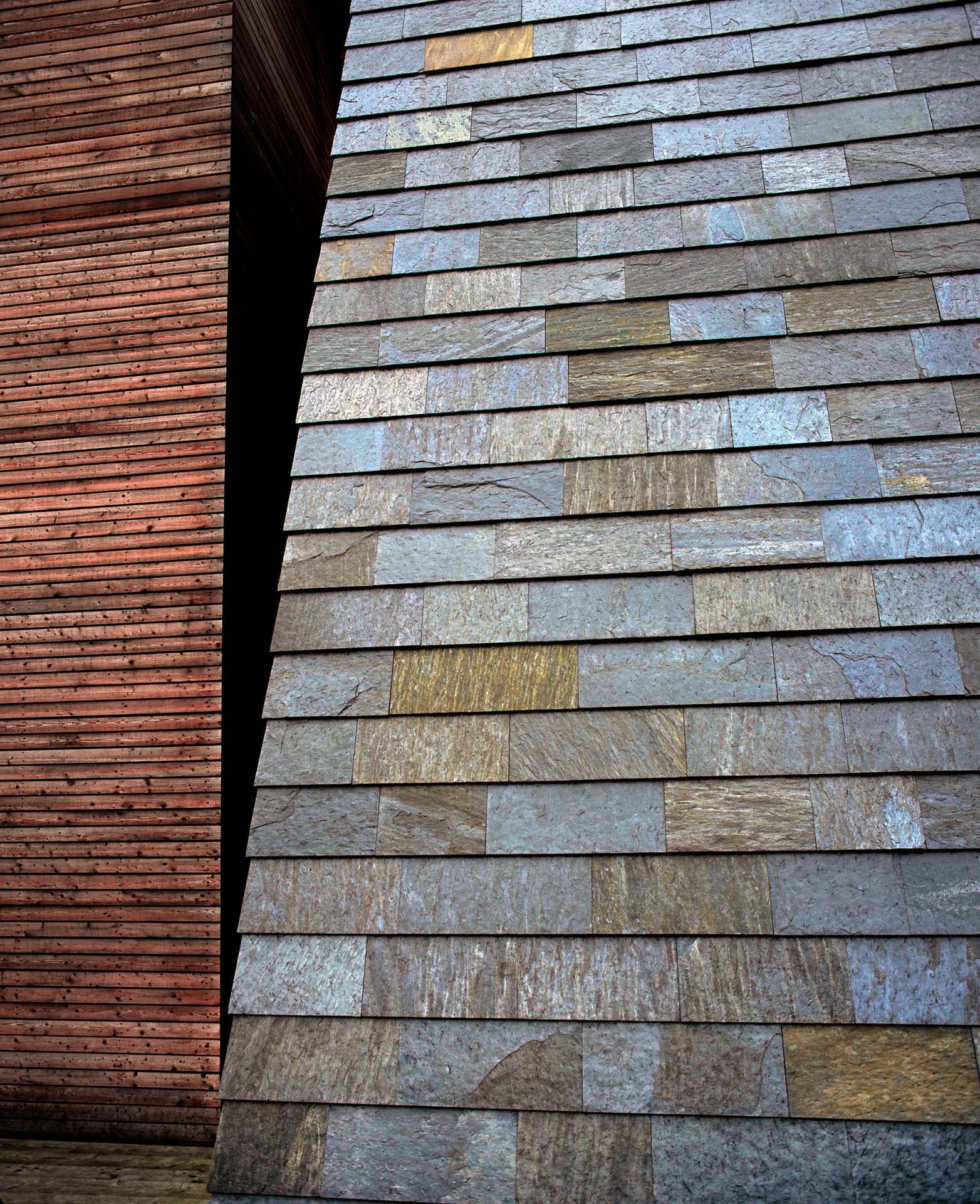 Bygg med fasade i Ottaskifer. Skiferflisene i rustfarge er kombinert med mørkt gyllent treverk.