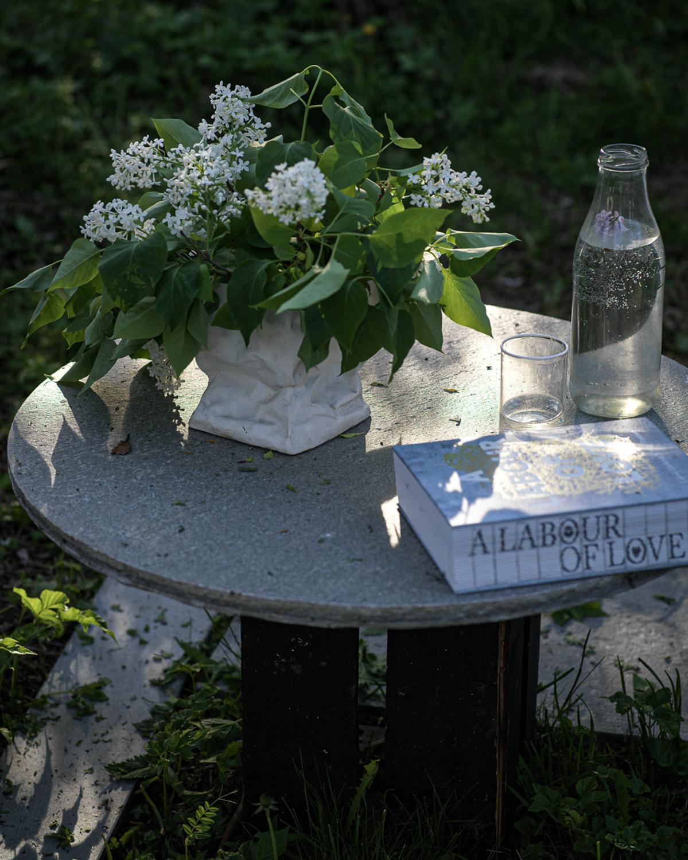 Et rundt steinbord av Oppdalskifer. På bordet står en plante, et glass og en bok.