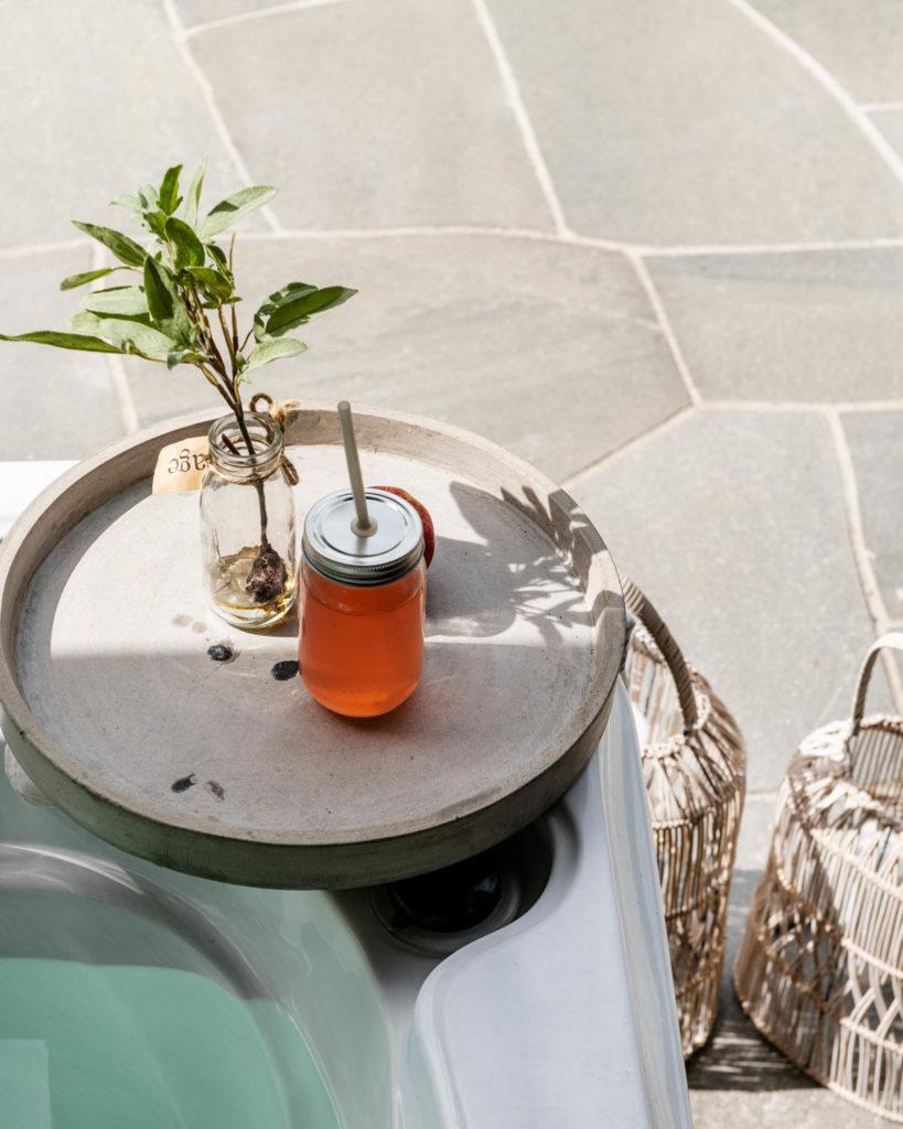 Bruddheller av lys Oppdalskifer på en terrasse med et brett med en sommerdring som står på kanten av et boblebad på en terrasse