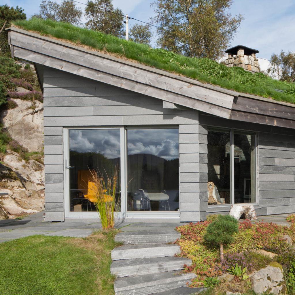 Hytte med fasadeskifer i lys Oppdal: tynne skiferplater på veggen. Grønne omgivelser rundt hytta.