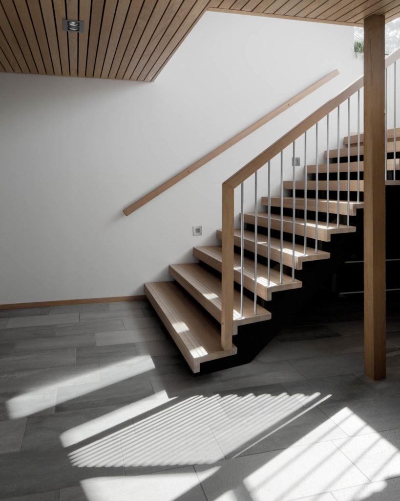 En entre / gang med grå fliser av silkebørstet Lys Oppdalskifer i på gulvet. En tretrapp går opp til høyre og kaster et skyggespill på skifergulvet.