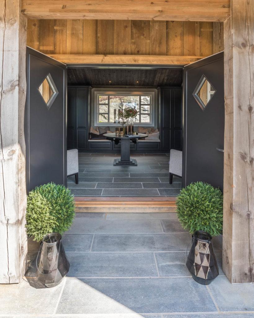 Et inngangsparti i en hytte med doble dører som er åpen og hvor man ser rett videre inn til en stor hall møblert med et rundt bord, benk og lenestoler. Det er grå fliser av Lys Oppdalskifer ute og som er videreført inn til den store entreen / gangen.