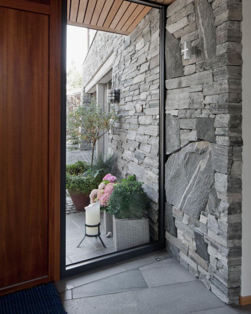 En entre hvor en ser ut gjennom vinduet i entreen. Mursteinveggen og de grå gulvflisene i lys Oppdalskifer er videreført sømløst ut.