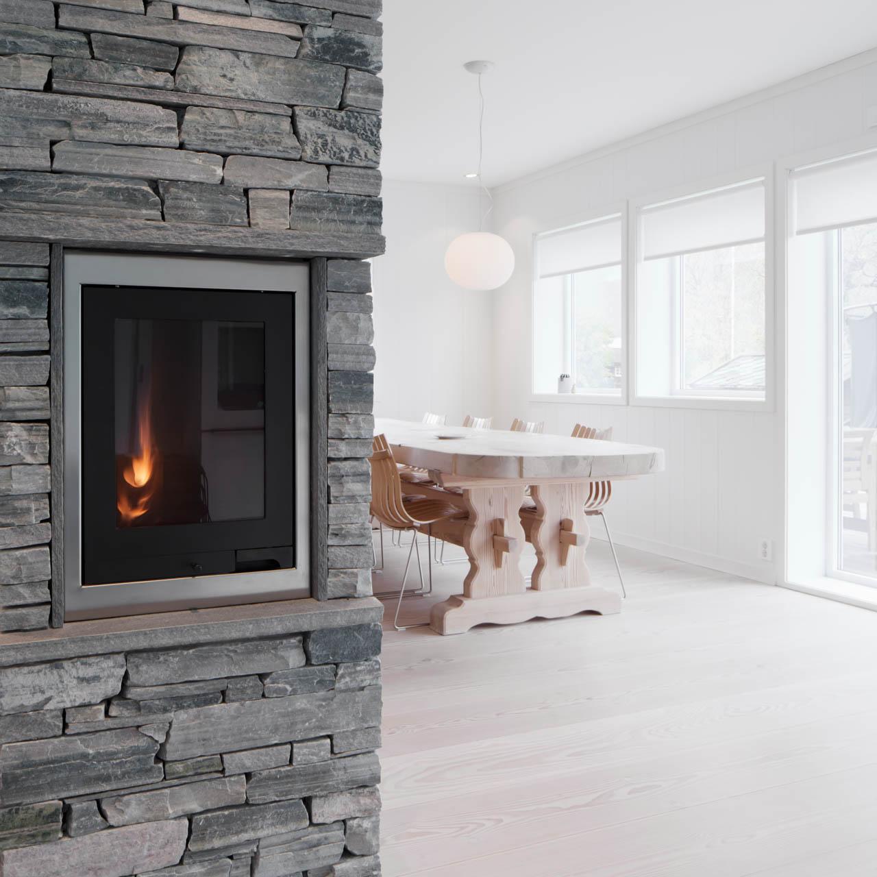 En stue med en peis av lys Oppdalskifer murstein (tørrmur). Rommet er hvitt og lyst og moderne med designkliassikere som Scandiastolen rundt spisebordet av lyst treverk