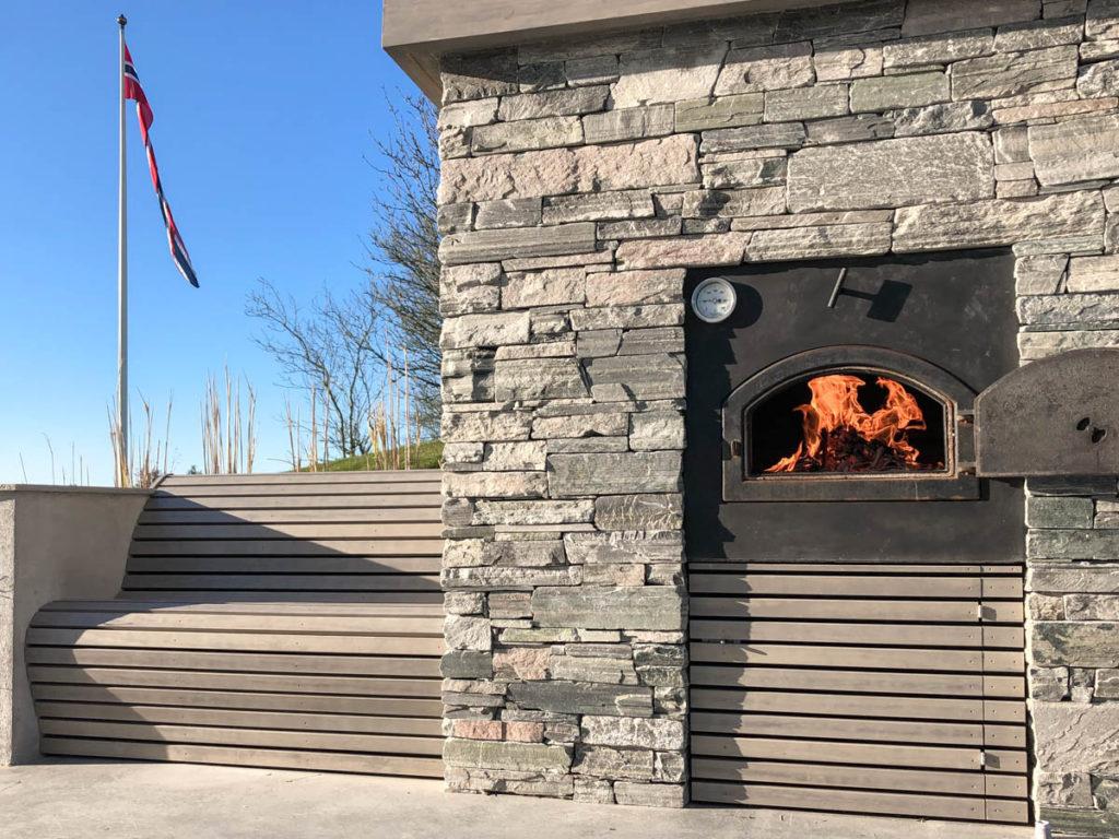 En terrasse med en bakerovn murt med lys Oppdalskifer murstein tørrmur med en benl i forlengelsen av pizzaovnen.