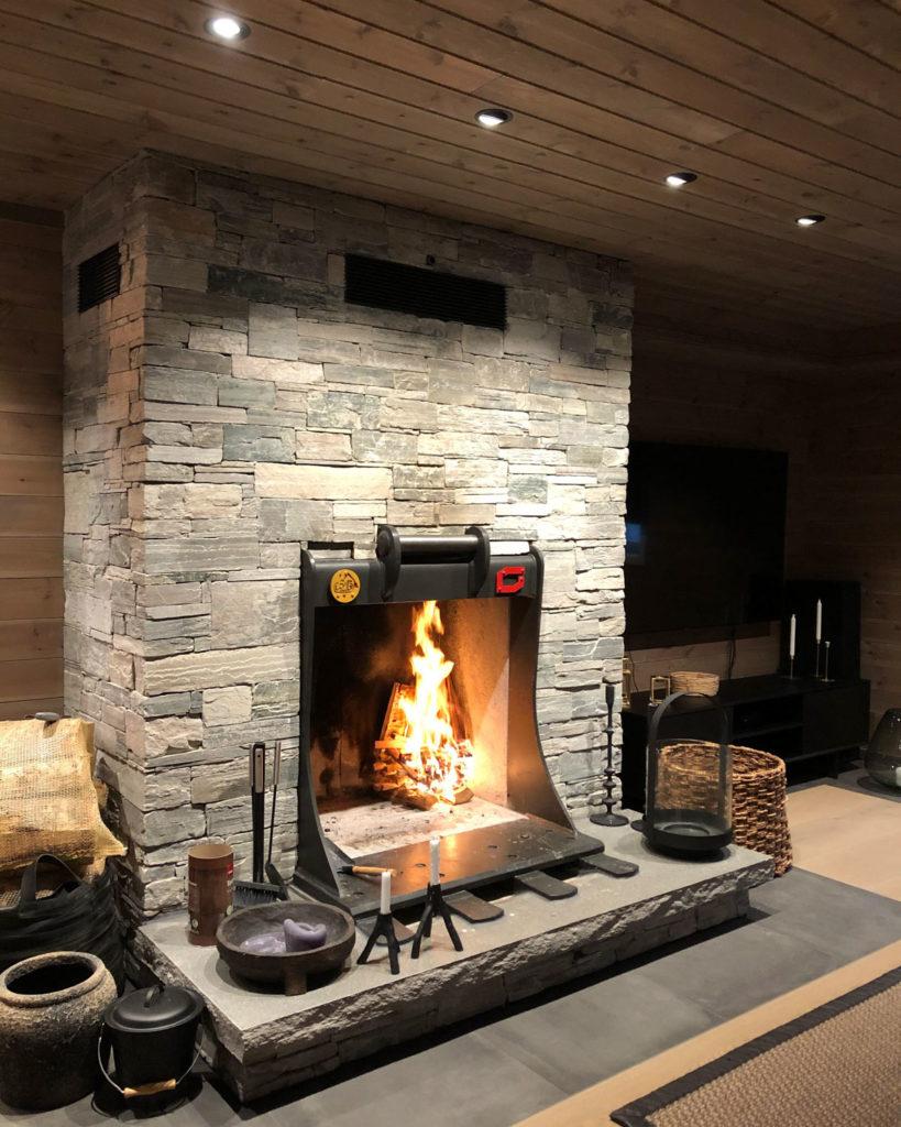 En hytte med en peis av Lys Oppdal skifer murstein tørrmur. Peisinnsatsen er formet som en gravemaskinskuffe.