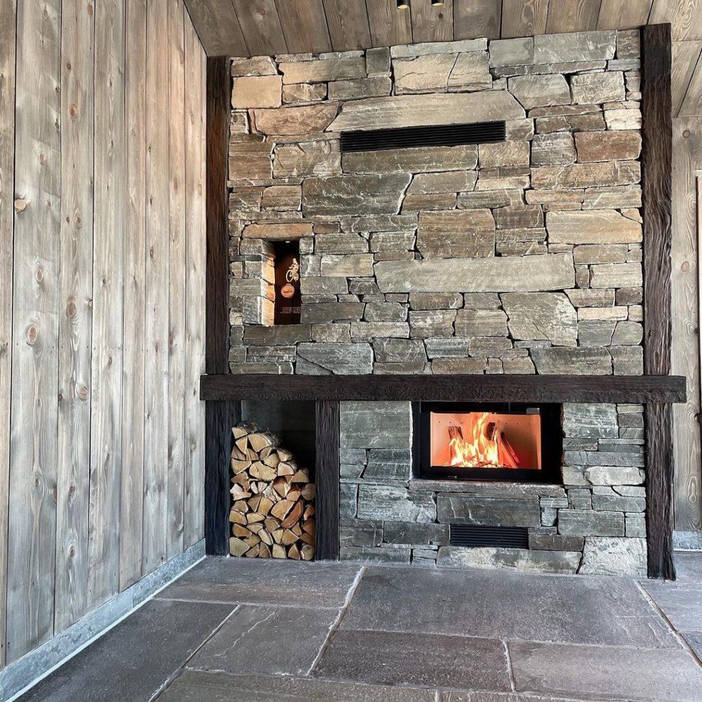 En hytte med en peis av Lys Oppdal skifer murstein tørrmur. I peisen er det innfelt rom for ved. Gulvet er av fliser Lys Oppdalskifer.