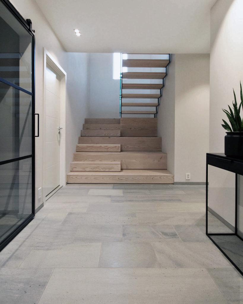 En entre / gang med grå fliser av silkebørstet Lys Oppdalskifer i på gulvet. En tretrapp er plassert i enden. Skap på venstre side har sotede glassdører med sort omramming.