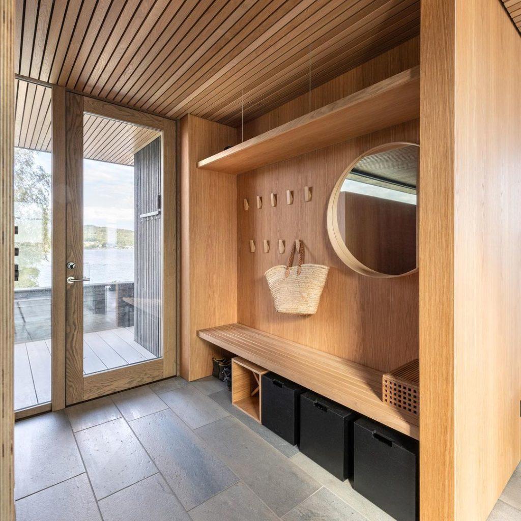 En entre i en moderne hytte med grå og antikkbørstede lys Oppdalskifer fliser på gulvet og med møbler i treverk. Designet av arkitekt Tommie Wilhelmsen
