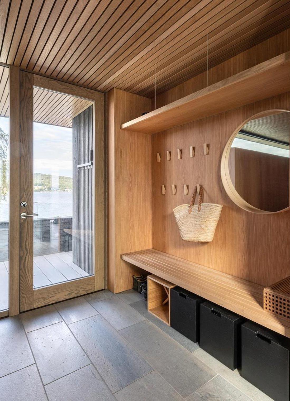En entre i en moderne hytte med lys Oppdalskifer fliser på gulvet og med møbler i treverk. Designet av arkitekt Tommie Wilhelmsen