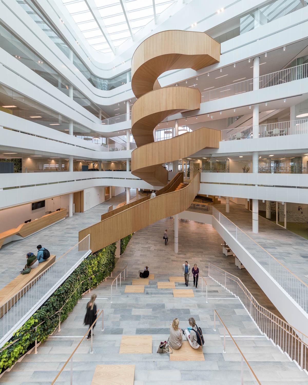 Inne på Segerstedhuset, Uppsala Univeristet med fliser av lys Oppdalskifer på gulvene. En stor spiraltrapp av tre går over flere etasjer bakerst i rommet