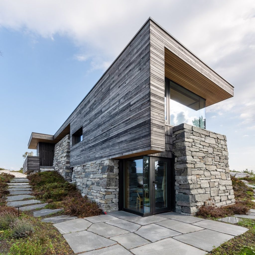 En moderne hytte med Lys Oppdalskifer / bruddheller,  tråkkheller og  mursteinsfasade på deler av hytten sammen med treverk. Tråhhhellestien med skifer går langs hytteveggen.04