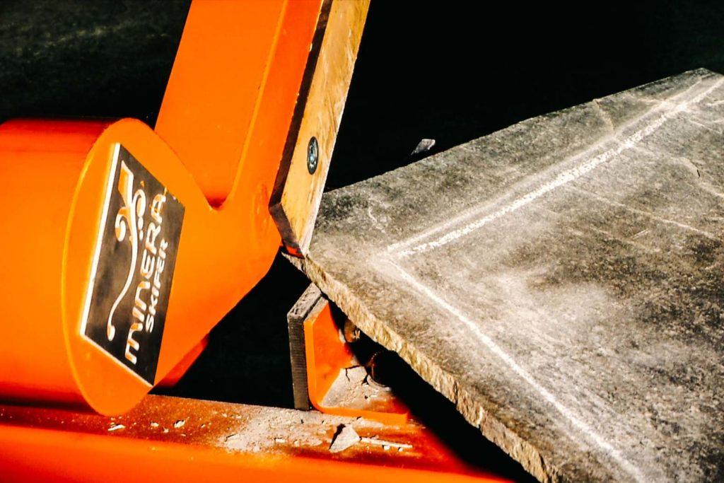 Et nærbilde av en Minera Skifersaks som klipper en bruddhelle av Oppdalskifer.