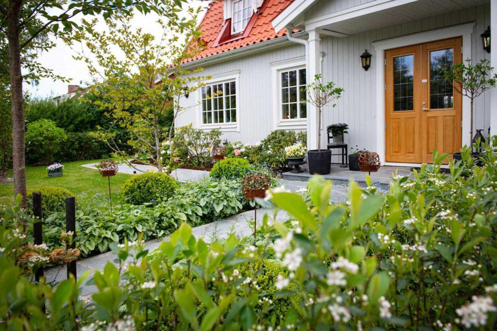 Et hvitt hus med bruddheller av Offerdalskifer rundt huset og som gangsti opp til huset