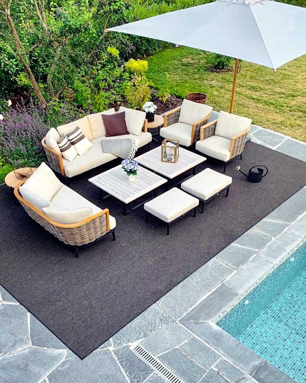 En terrasse med svømmebasseng belagt med bruddheller av Offerdalskifer. På terrassen er det et utendørsteppe, parasoll g en stittegruppe