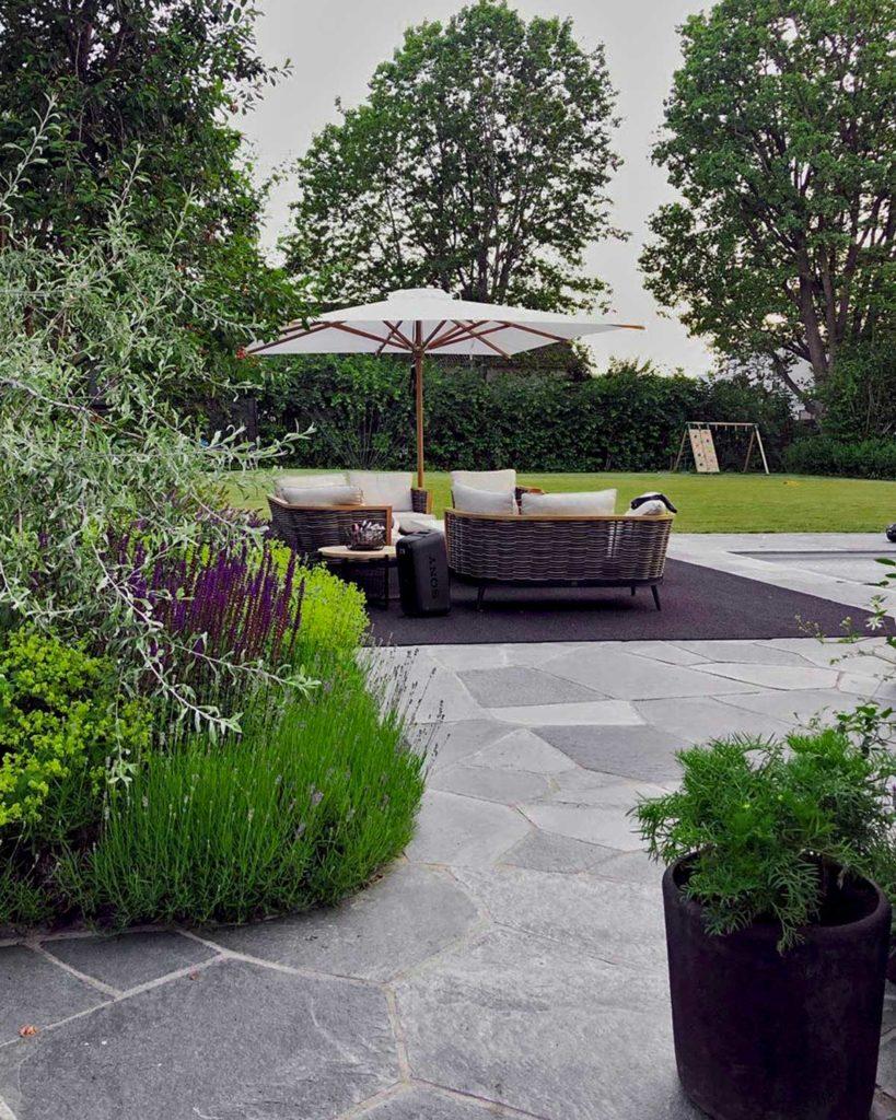 En terrasse belagt med bruddheller av Offerdalskifer. På terrassen er det et utendørsteppe, parasoll g en stittegruppe: Vakker beplantning omkranser terrassen