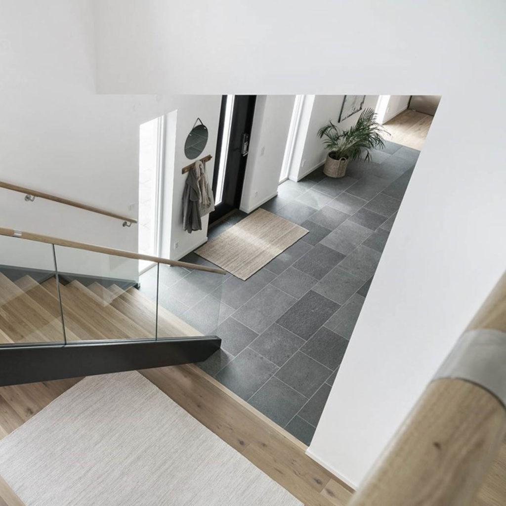 Et inngangsparti med grå skifer i gangen. Offerdal skiferflis på gulv gir en kontrast til hvite slette vegger og en harmoni til treverket i trapp og tilstøtende gulv.