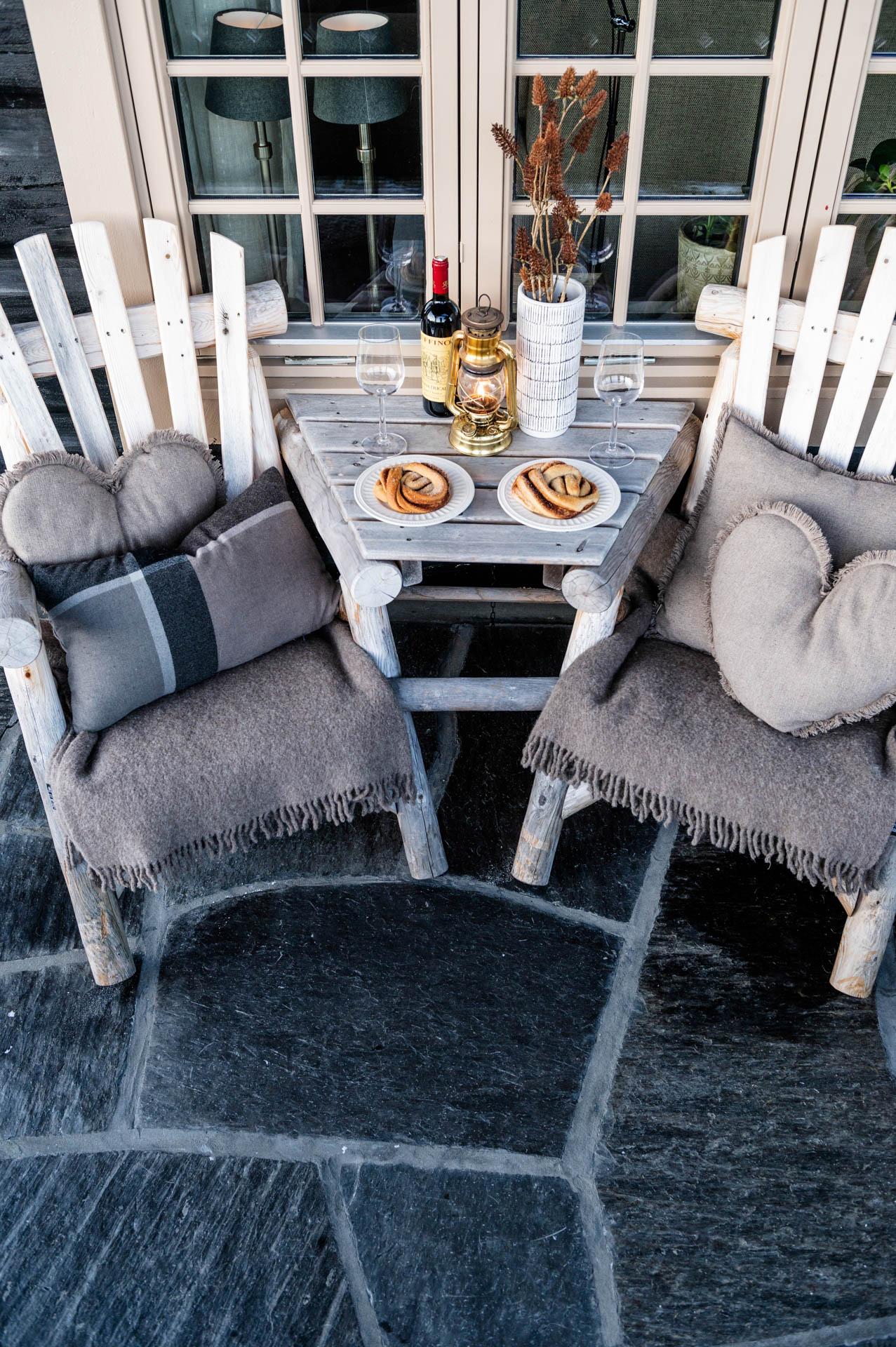 En uteplass med sort Otta Pillarguri bruddskifer hvor bordet er dekket til kos med vin.