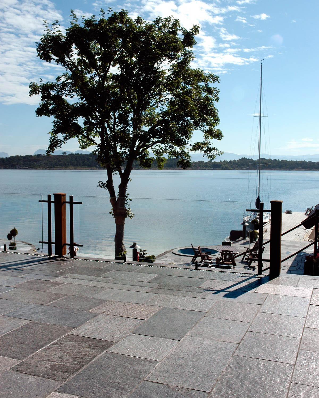 En terrasse ved sjøen med utefliser i brun skifer. Ved plattingen av Ottaskifer er det et stort tre og en båt fortøyd ved bryggen.
