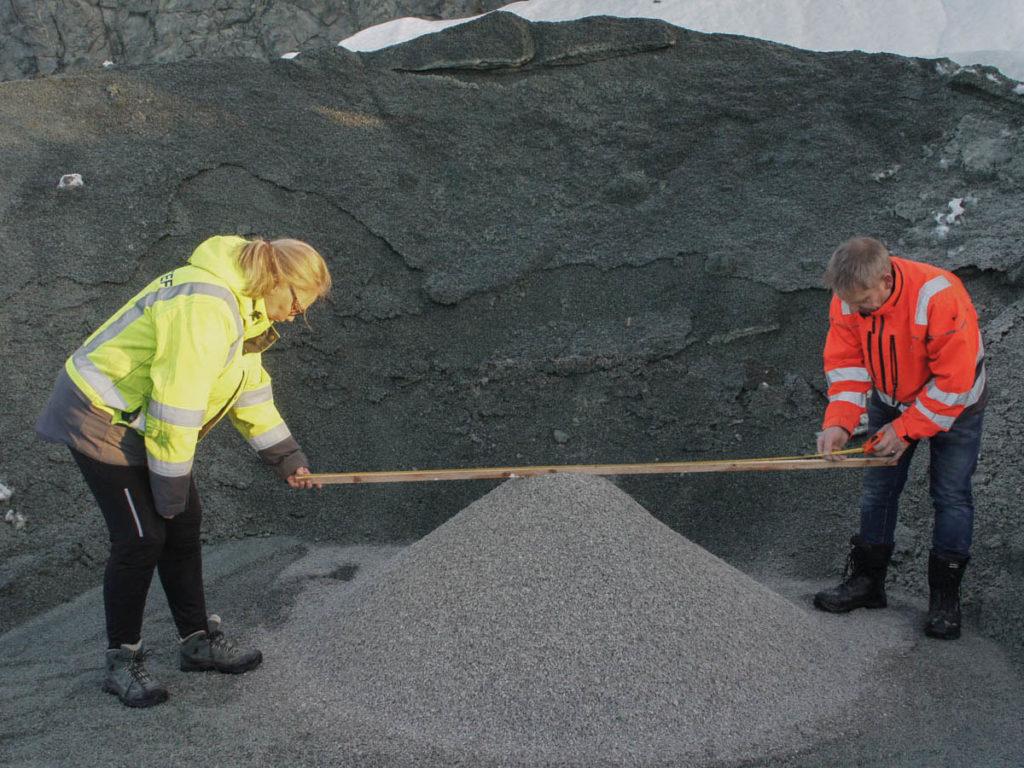 2 personer fra Sintef gjør noen målinger på en haug med knust skifer i forbindelse et forskningsporsjekt kalt SkiferUnik hvor en forsøker å utnytte knuste rester fra skiferproduksjon til bygningsformål i en bærekraftig løsning.