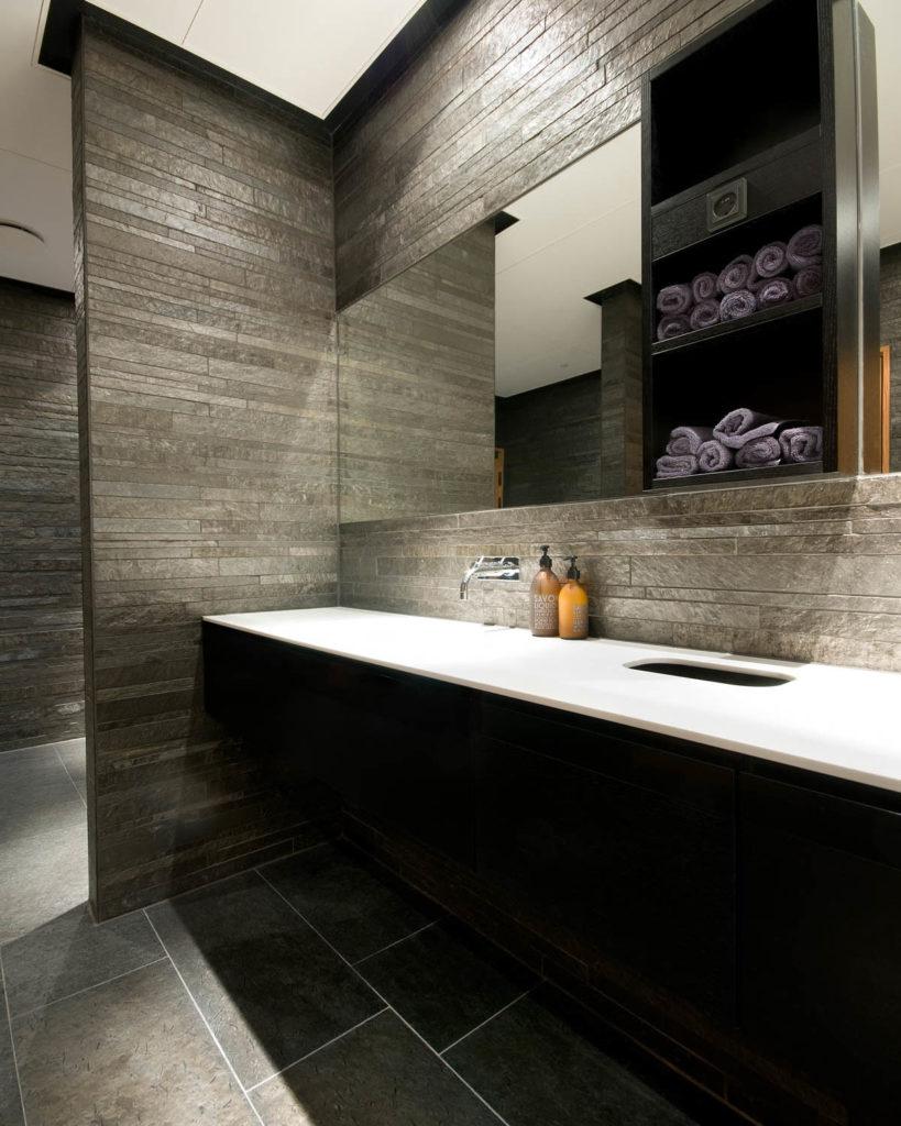 Et bad med smale fliser, strips, av Ottaskifer på vegg og fliser i større format av norsk skifer fra Otta på gulv. badet har en stor vask med hvit benkeplate.