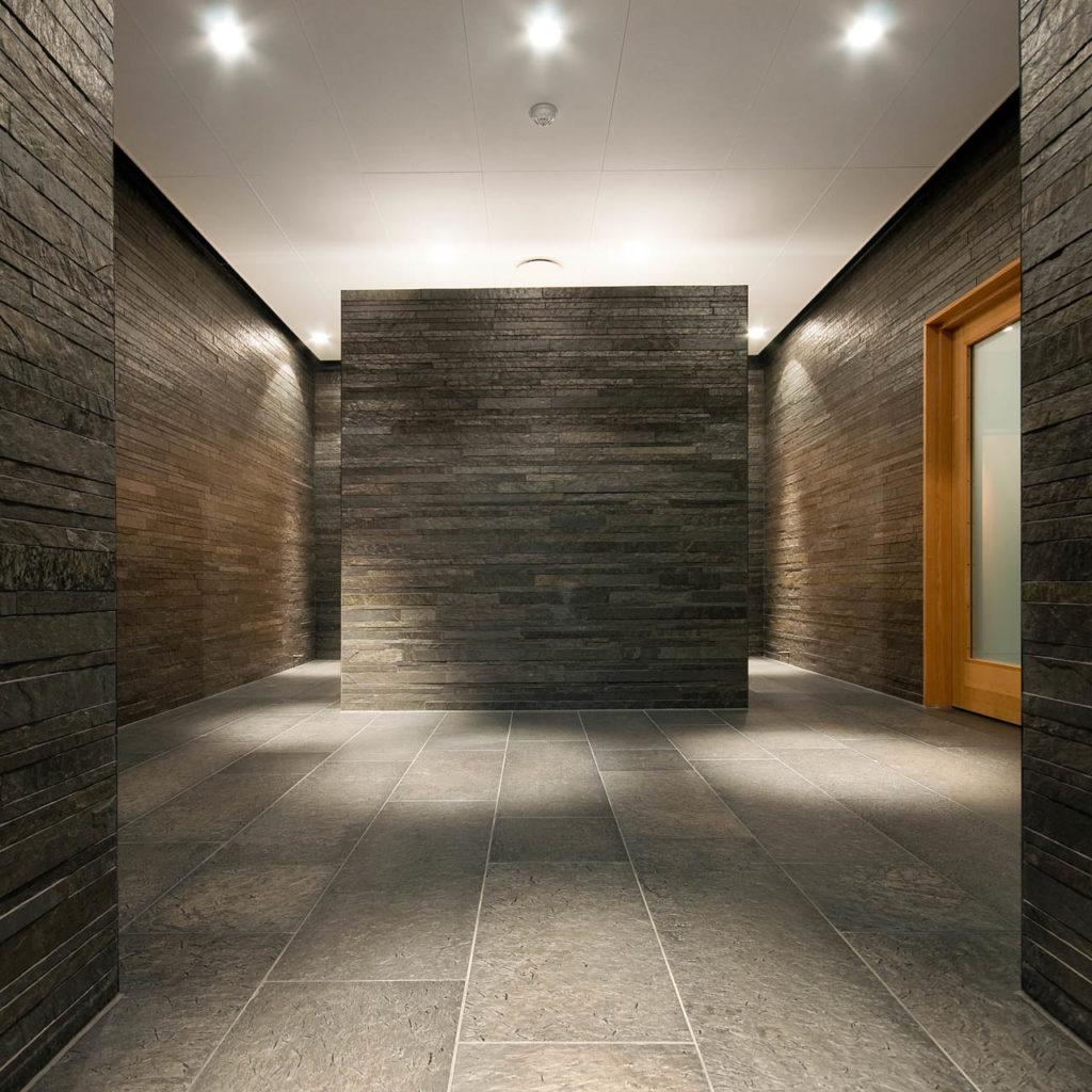 Et stort rom med sort skiferflis fra Otta Pillarguri på gulvet. Midt i rommet står en skifermur som romdeler i Otta tørrmur.