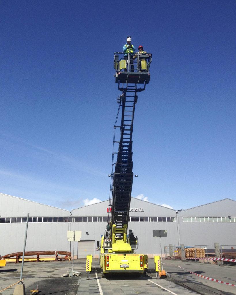 En høy kran med en mann på toppen som skal slippe en jernkule ned på offerdalskiferen for å teste dens styrke