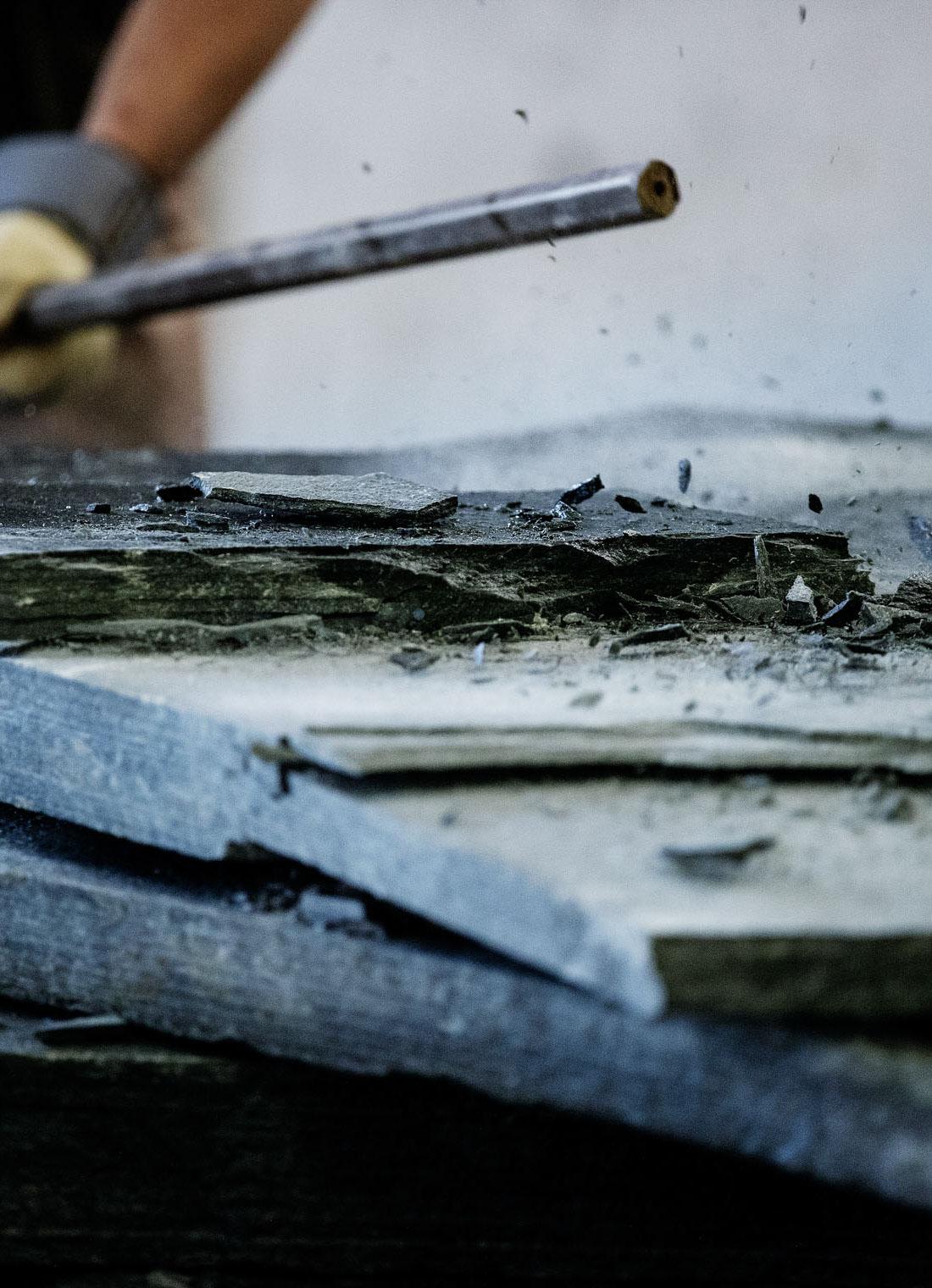 En steinhugger hos skiferprodusenten Minera Skifer som slår med et spett (kalt sveiping) på en skiferplate av Offerdalskifer