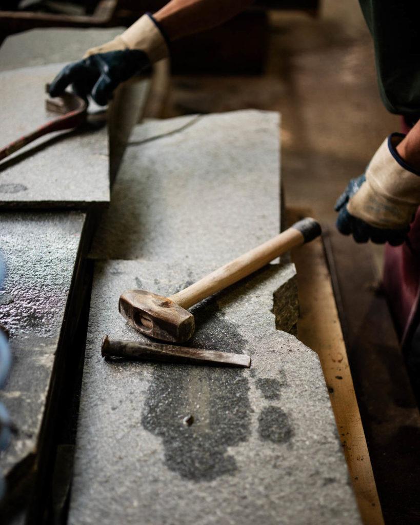 En steinhugger hos Minera Skiffer Offerdal som bearbeider Offerdalskifer med hammer og kiler