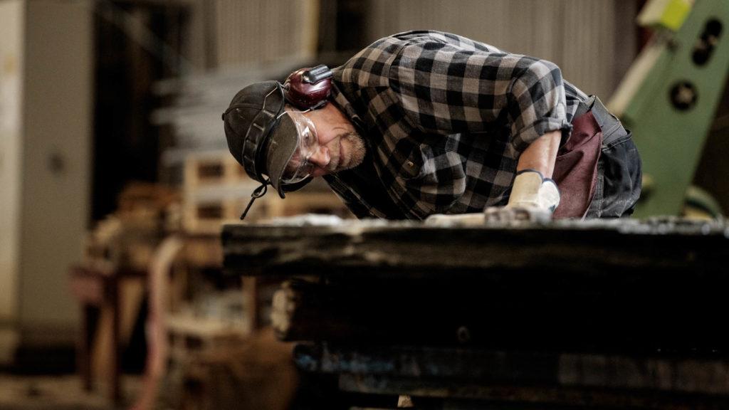 """En steinhugger hos Minera Skiffer Offerdal som vurderer og """"leser"""" skiferblokka for å se hvordan den best kan utnyttes"""