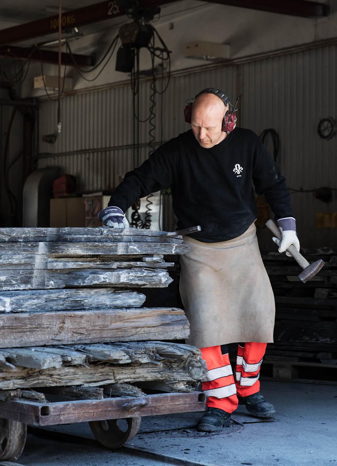 En skiferhugger med skinnforkle og hammer som står foran en steinblokk av Ottaskifer Pillarguri for å kløve denne i skiferplater.