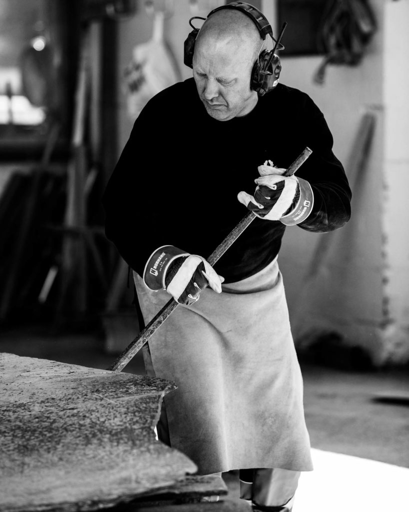 Steinhogger hos Minera Skifer kløver store plater av Ottaskifer inne produksjonshallen