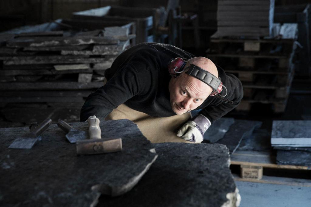 Steinhogger hos Minera Skifer vurderer steinblokka før han skal til å kløve den store platen av Ottaskifer inne produksjonshallen