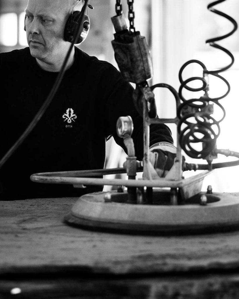 Steinhogger hos Minera Skifer kløver store plater av Ottaskifer inne produksjonshallen. På bildet løftes en stor plate med en vakuumløfter