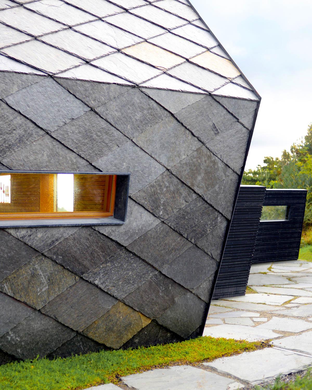 En hytte med firkantheller av Ottaskifer både på tak og fasade med en sømløs overgang. skiferen begynner å bli gylden, rustfarget.
