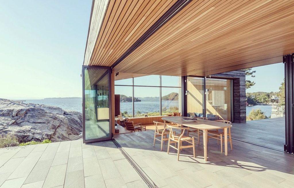 En moderne hytte som har fliser av lys Oppdalskifer i en sømløs overgang fra spisestue og terrasse. Spisestuen har store glssdører som kan trekkes fra slik at spisestuen blir en del av terassen. Samme materiale inne og ute!