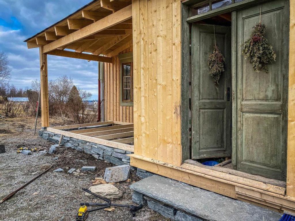 Et hus som viser en tom terrasse med takoverbygg som skal bli til et utekjøkken bygd på en grunnmur av skifer.