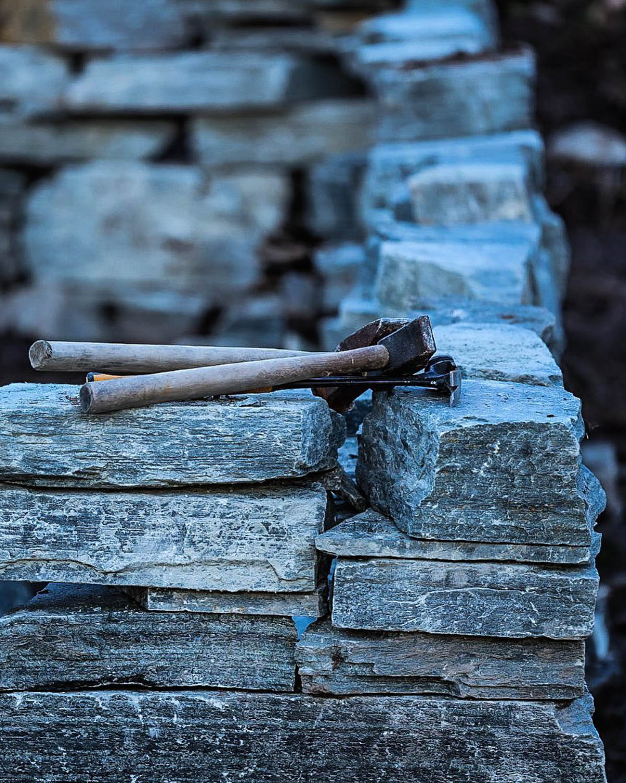 En grunnmur tørrmur av Offerdal skifer som er under bygging. Oppe på muren ligger hammer og meisel.